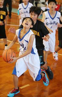 熱戦を繰り広げた八重山選抜男子と松山國民小学(白)=21日午後、平真小学校体育館