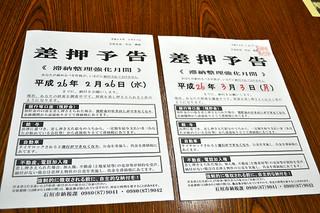 市内の民家の郵便受けに入っていた予告書(左)と公印が押された石垣市発行の予告書=26日夕、市役所庁議室