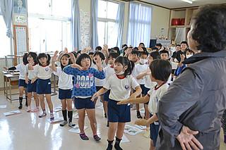 宮良小学校の方言教室で「月ぬ美しゃ」を踊る1、2年生たち=26日午前、同校