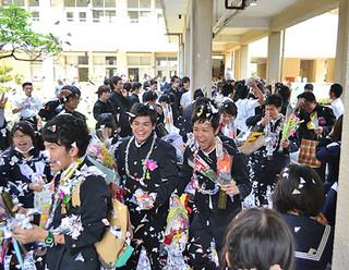 大勢の在校生がつくる花道を笑顔で学び舎を巣立つ卒業生ら=1日午前、八重山高校