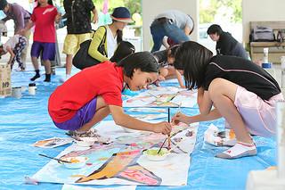 飛行機を描くアートワークショップでデザインを楽しむ参加者たち=1日午後、石垣市役所ピロティ