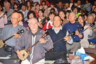 「さんしんの日」にちなんで約250人が参加して開催されたサンシン大合奏会=4日午後、八島小学校体育館