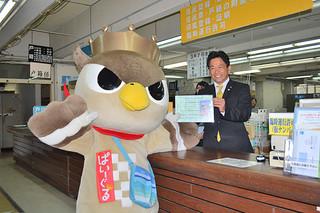中山市長から特別住民登録証を受け取るぱいーぐる(左)=7日午後、市役所