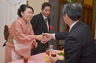 大勢の来場者から祝福を受けた新城美保さん(左)と夫の正之さん(奧)=8日午後、ホテル日航八重山