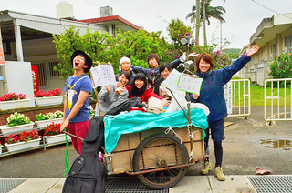 リヤカーを引きながら旅を楽しんでいる大学生の男女7人=13日午後、野底小学校前