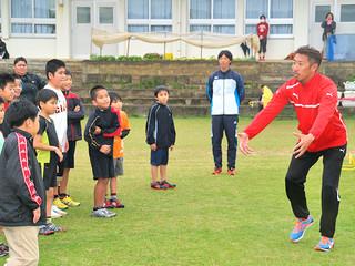 ハードル競技について指導する中京大学陸上部監督の吉岡さん(右)=6日、与那国小学校グラウンド
