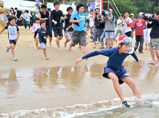 テープカットとともに一斉に海に駆け出す子どもたち=16日午前、西表島トゥドゥマリの浜