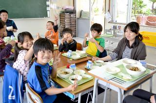 新給食センターから配送された給食に喜ぶ名蔵小中学校の児童ら=17日午後、同校