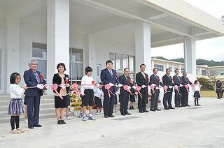 新体育館の完成を祝って、テープカットする児童や関係者ら=21日午後、上原小