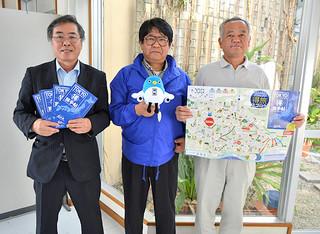 成田観光ガイドブックを手に成田市の魅力をPRする関係者ら=25日午後、八重山毎日新聞社