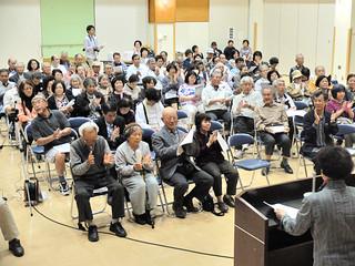 決議文に拍手で賛同する参加者たち=26日午後8時ごろ、石垣市健康福祉センター