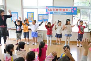 真喜良第2団地自治会室で行われた児童館活動でダンスをする子どもたち=3月6日。子育て支援制度は、2015年度から大きく変わる