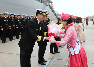 ミス八重山から花束を受ける湯浅秀樹司令官(左)ら=3月31日午前9時15分ごろ、石垣港