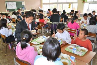 市立学校給食センター開所後初の給食を登野城小学校の4年生と一緒に楽しむ中山義隆市長(左)ら=7日午後、同校