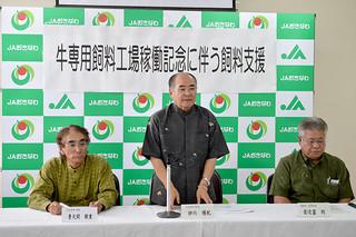 県内で牛専用飼料工場が再稼働したのを記念して飼料価格の支援を発表する砂川博紀理事長(中央)=7日午後、JA会館