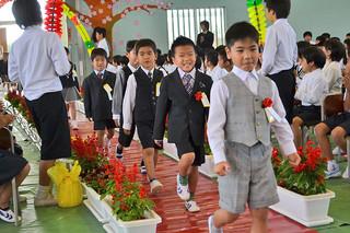 大浜小学校の入学式で、アーチをくぐり笑顔で入場する新1年生たち=8日午前、同校体育館