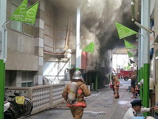 火災現場から黒煙が上がる中、消火活動に向かう消防士ら=読者提供・15日午前9時45分ごろ