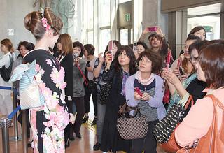 新城さんが仕上げた着付けモデルに見入る来場者たち=15日午後、浦添市てだこホール