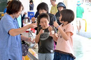 「もずくの日」のイベントでモズク流しを楽しむ子どもたち=20日午後、JAファーマーズマーケットゆらてぃく市場前