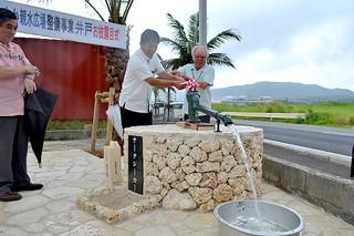 ポンプを使って井戸から水をくみ上げる大工さん(右)と中山市長=22日夕、新川川なたつ橋西側