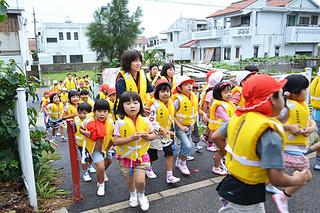 避難訓練で真栄里公園に向けて走る八島小学校の児童ら=24日午前、同校近くの避難道路