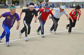 沖縄竹富郷友会の第54回親睦大運動会で白熱のレースをみせた中学生以上の200㍍走=27日、石嶺小学校グラウンド