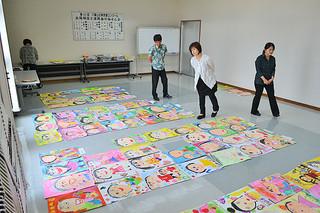 幼稚園・保育所の部の作品から入賞作品を選ぶ審査員ら=29日午前、八重山毎日新聞社会議室