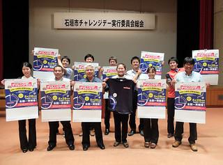 チャレンジデーのポスターを手に多くの市民の参加を呼びかける実行委員会事務局の職員たち=2日夕、市民会館中ホール