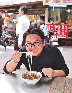 「美食とダイエットのせめぎあいだ」と語りつつ、排骨麺(骨付きブタバラ肉を載せた麺)をすする小笹さん=4月29日、県産業振興公社台北事務所近くの屋台