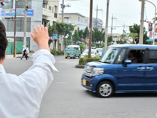 街頭で手を振る立候補予定者の1人=3日、730交差点=。市議選はすでに動きだしている