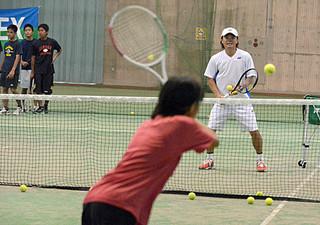 子どもたちにテニスを指導する元プロの本村剛一さん(奥)=5日午前、市中央運動公園屋内練習場