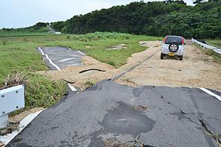 大雨ではがれたアスファルトが畑に流れ込んだ白保の農道=6日午後、轟川上流の牧那橋付近
