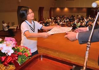 高学年の部最優秀賞で黒島社長から表彰状を手渡される児童ら=10日午後、市民会館中ホール