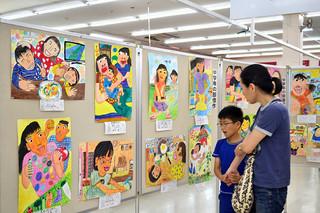 素敵なお母さんの図画コンクールの入賞作品が展示されているマックスバリュやいま店=13日午後
