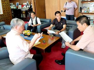 中山市長(右)に台湾歌舞団石垣島公演の日程などについて報告する石垣会長(左)ら八重山・台湾親善交流協会の役員=14日午後、市長室