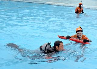 合同訓練で海保の潜水士の指導で必死に泳ぐ消防士=16日午後、市営プール