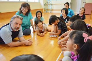 子どもたちに英語の発音を教える野崎旬子、マンリー・スロー夫妻(左側2人)=17日夕、石垣市子どもセンター