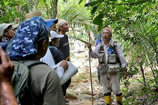 自然観察会で、講師の渡辺賢一氏(右)から説明を受ける参加者たち=18日午前、於茂登岳