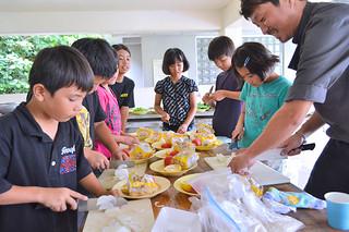 原田さん(右)の指導でハーブを使った魚料理やオリジナルカレーづくりに挑戦する大浜小の児童ら=21日午後、県立石垣青少年の家