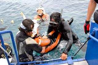 石垣海上保安部の潜水士の指導を受けながら、海難救助の訓練に取り組む人たち=22日午後、上原港沖合