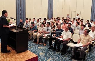 石垣市観光交流協会の総会で、宮平康弘会長(左)のあいさつを聞く会員ら=22日夕、ホテル日航八重山