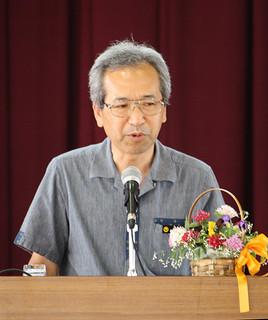 伊原間中学校の開校記念集会で講話し、後輩にエールを送った崎山八郎さん=28日午後(同校提供)