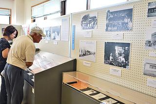 当時の写真を懐かしそうに見入る金城政光さん=5月31日午前、八重山平和祈念館展示室