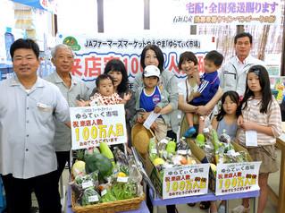 買い物客100万人目となった宮良政美さん(左から3人目)ら=2日午前11時すぎ、JAファーマーズマーケットゆらてぃく市場