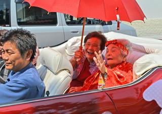 カジマヤーパレードで沿道の人たちに笑顔で手を振る徳山静子さん=4日午前、宮鳥御嶽前