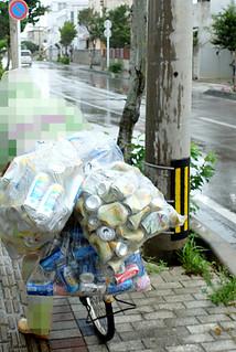 資源ごみの収集日にアルミ缶を集めて回るお年寄り。雨の日も雨がっぱを着けて回収する=5月13日、石垣市内