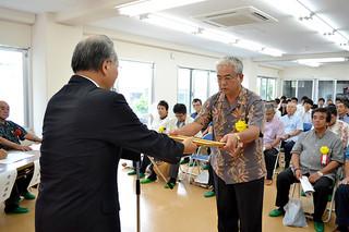 八重山高校学校寮の落成式典で、本成浩校長(左)から感謝状を受け取る受賞者=7日午後、同寮