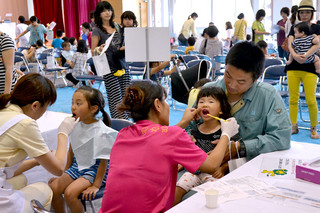 第37回デンタルフェアで、歯の磨き方の指導を受ける親子ら=7日午後、市健康福祉センター