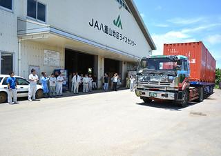 八重山産ひとめぼれの1期米を積んだトラックを拍手で送り出した出荷式=16日午後、JA八重山地区ライスセンター構内