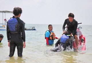 琉球水難救済会が実施した救助訓練で水上バイクに要救助者を引き揚げる際の指導を受ける参加者ら=19日午後、フサキリゾートヴィレッジ